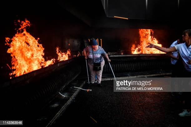 TOPSHOT A woman walks near the fire where people throw candles at the Fatima shrine in Fatima central Portugal on May 12 2019 Thousands of pilgrims...