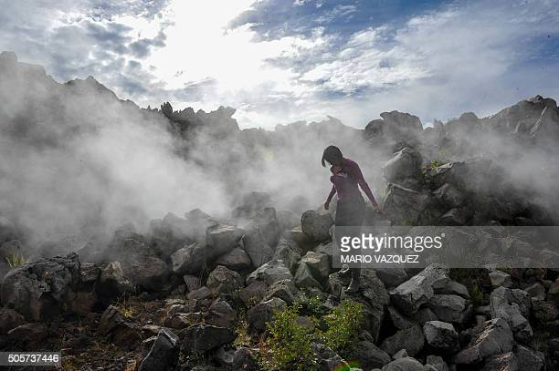 A woman walks near the Paricutin volcano in Angahuan Michoacan State Mexico on January 17 2016 The town of San Juan Parangaricutiru was destroyed in...