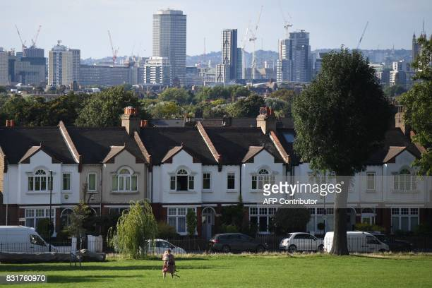 A woman walks newar a row of houses in London on August 13 2017 The average price of a house in the UK increased by 49% in the year to June according...