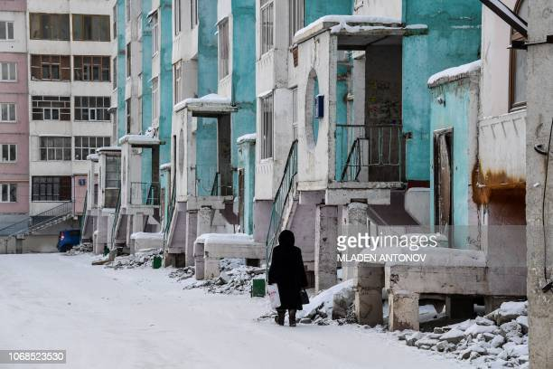 A woman walks next to a cracked panel apartment building in the eastern Siberian city of Yakutsk on November 26 2018 Many houses in Yakutsk are made...