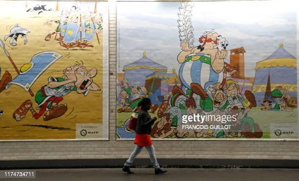 A woman walks next to a draw especially designed to commemorate the 60th anniversary of France's famous comic characters Asterix and Obelix on...
