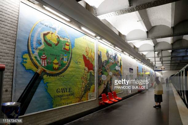 A woman walks next to a drawing especially designed to commemorate the 60th anniversary of France's famous comic characters Asterix and Obelix on...