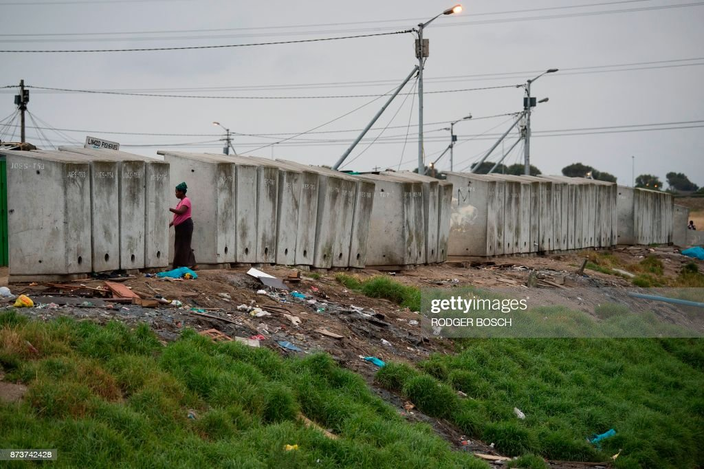A woman walks next to a line of toilets in an informal settlement in Langa, a mostly impoverished township, about 10km from the centre of Cape Town, on November 12, 2017. /