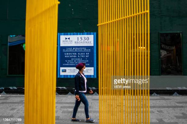 A woman walks next to a poster of a retail space to rent in Times Square on August 8 2020 in New York City With more than four months NYC has closed...