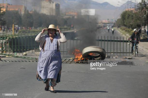 A woman walks next to a road blocked by supporters of Evo Morales Ayma as clashing with police during protests on November 19 2019 in El Alto La Paz...