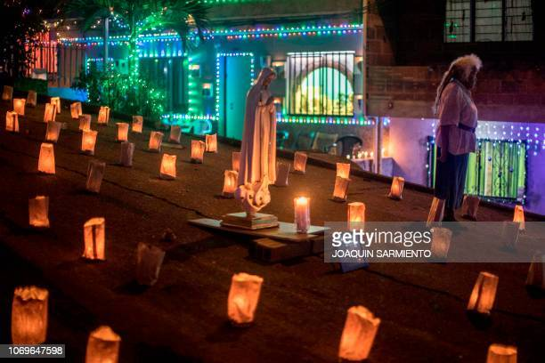 A woman walks next to a Virgin Mary sculpture during the Day of the Little Candles celebrations in Medellin Colombia on December 7 2018 The Day of...