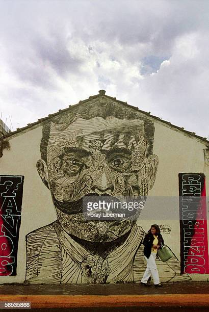 A woman walks next to a wall painting of Emiliano Zapata the Mexican revolutionary form the 19th century March 9 2001 in San Cristobal Mexico The...