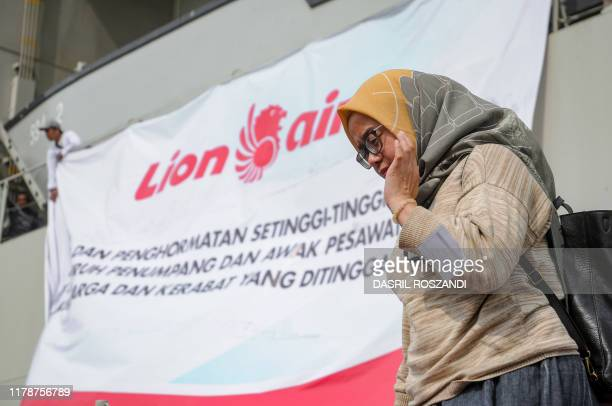 A woman walks off a navy ship at a base in Jakarta on October 29 after attending a ceremony for victims of a Lion Air plane crash in 2018 Grieving...