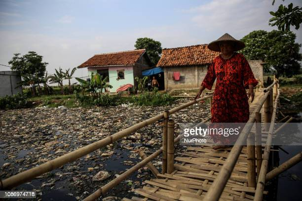 A woman walks on a bridge above a river covered by garbage in Bekasi West Java Indonesia on Wednesday January 8 2019 Plastic pollution in Indonesia...