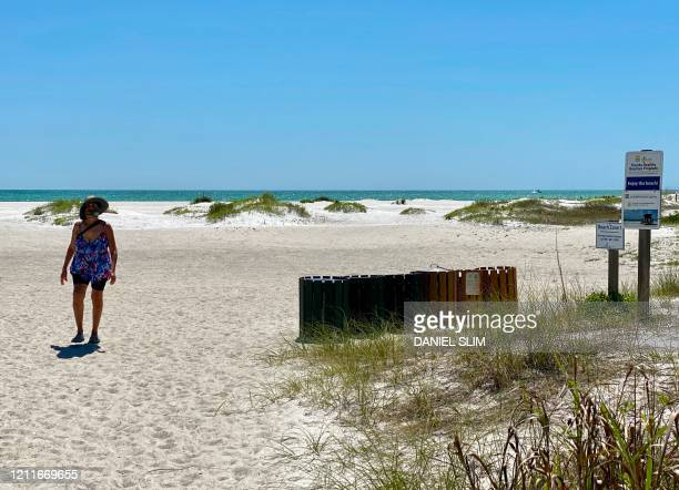 A woman walks on a deserted Lido beach Key off the coast of Sarasota Florida on May 3 2020