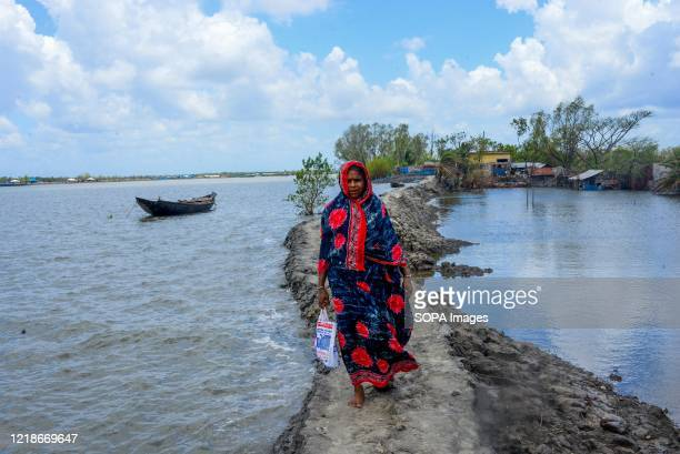 Woman walks on a flooded footpath during the aftermath of the extremely severe cyclonic storm Amphan. Thousands of shrimp enclosures have been washed...