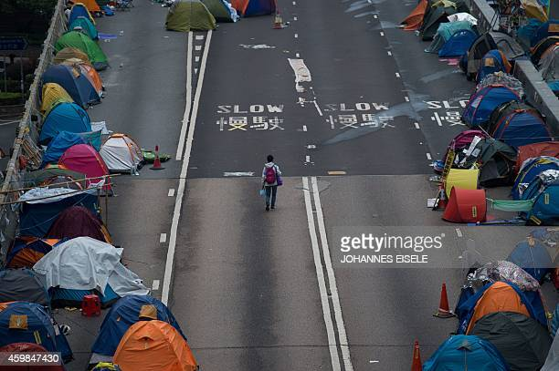 A woman walks on a flyover at the prodemocracy movement's main protest site in the Admiralty district of Hong Kong early on December 3 2014 The...