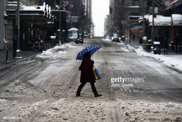 A woman walks on a nearly deserted street in New York's Times Square what is normally a crowed morning rush hour after a snowstorm on January 27 2015...
