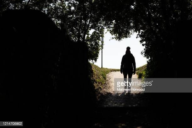 A woman walks on a pathway at Barry Island on March 25 2020 in Barry United Kingdom The Coronavirus pandemic has spread to at least 182 countries...