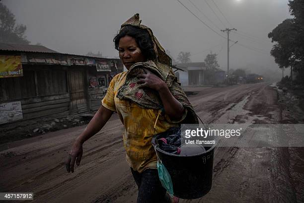 A woman walks on a road covered with ash following a further eruption of the Mount Sinabung on October 13 2014 in Berastagi Karo district North...
