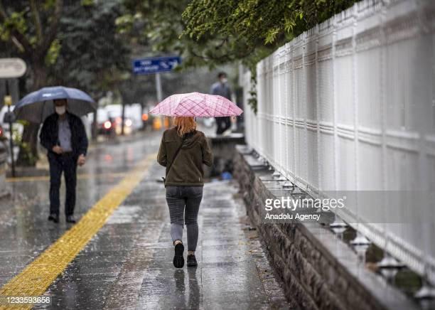 Woman walks on a sidewalk holding an umbrella during rainfall in Ankara, Turkey on June 22, 2021.