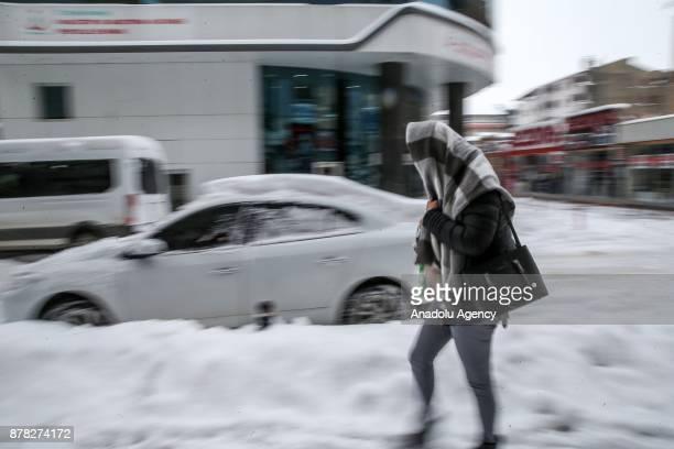 A woman walks on a snowy road after heavy snowfall in Van Turkey on November 24 2017