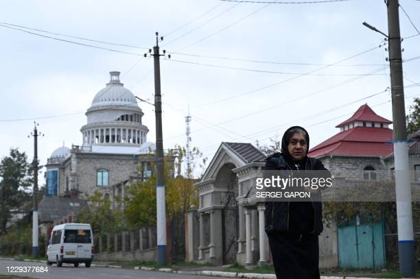 Woman walks on a street not far from a building, that somewhat resembles the US Capitol in Washington, in the Gypsy Hill quarter in the town of...