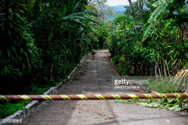 A woman walks on a street that has been closed down to vehicles by locals during government issued lockdown on May 18 2020 in Cuscatlan El Salvador...