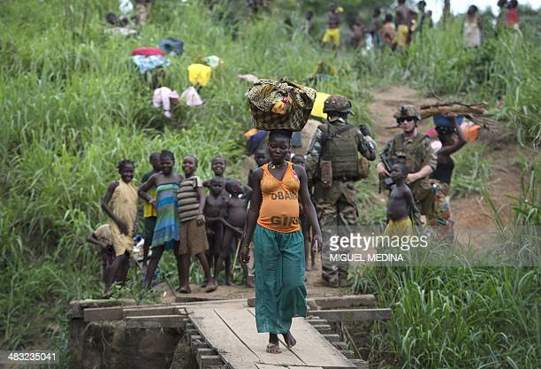 A woman walks on a wooden bridge as she crosses a river near the northwestern city of Boda on April 7 2014 The crisis in the strifetorn Central...