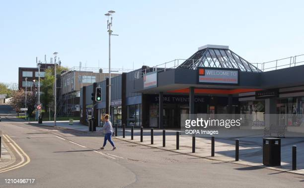 Woman walks on an empty Brackla Street during the lockdown. The UK government-imposed nationwide lockdown as a preventive measure against the spread...
