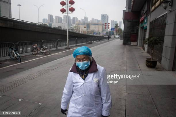 A woman walks on an empty road on January 27 2020 in Wuhan China As the death toll from the coronavirus reaches 80 in China with over 2700 confirmed...