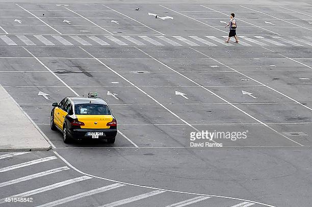 A woman walks on an empty taxi stop at the Barcelona Sants Train Station during a 24 hours cabs strike against Uber Taxi app on July 1 2014 in...