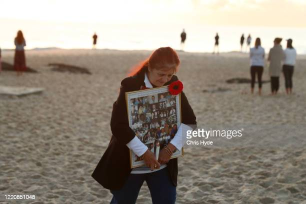 A woman walks on Currumbin Beach to commemorate Anzac Day on April 25 2020 in Gold Coast Australia Traditional Anzac Day ceremonies have been...