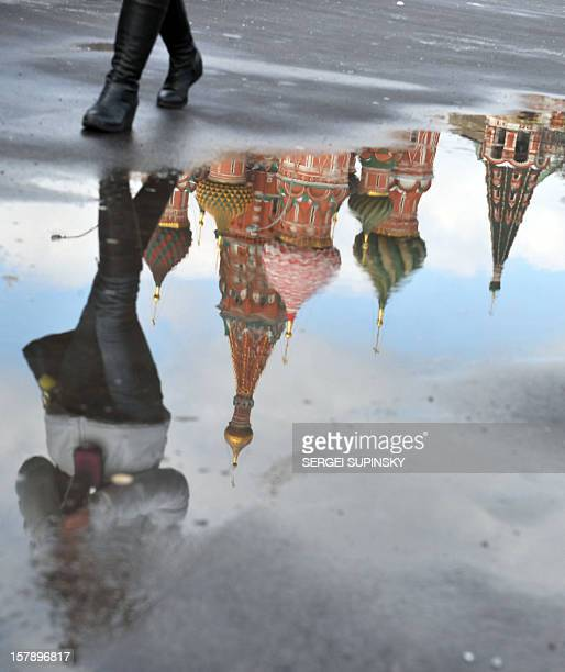 A woman walks on February 29 2012 near the Vasiliy Blazhenyi Cathedral reflected in a puddle in Moscow Russian Prime Minister Vladimir Putin is...