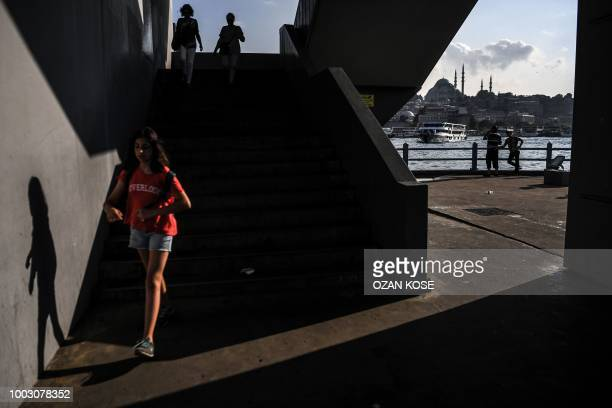 A woman walks on Galata Bridge in front of the Suleymaniye mosque in the district of Eminonu in Istanbul on July 21 2018