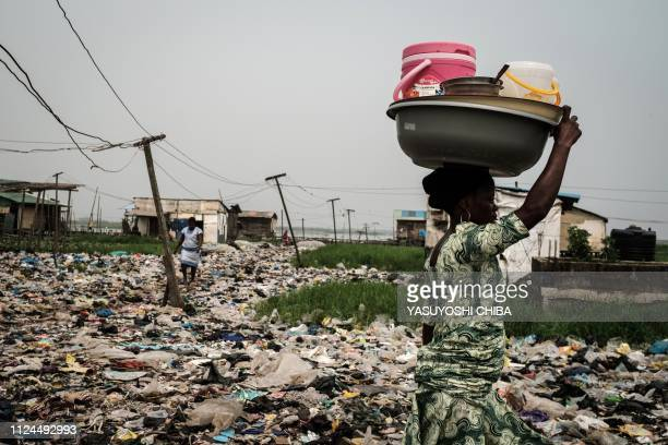 Woman walks on plastic waste, used to reclaim a swamp so that the land can be developed for housing, in the Mosafejo area of Lagos on February 12,...