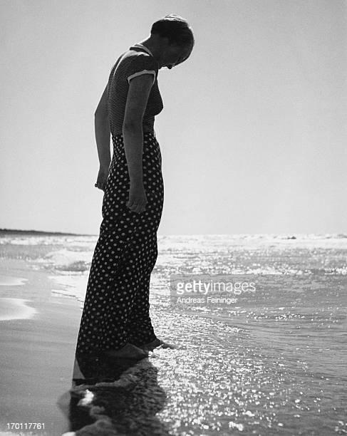 A woman walks on the beach 1934
