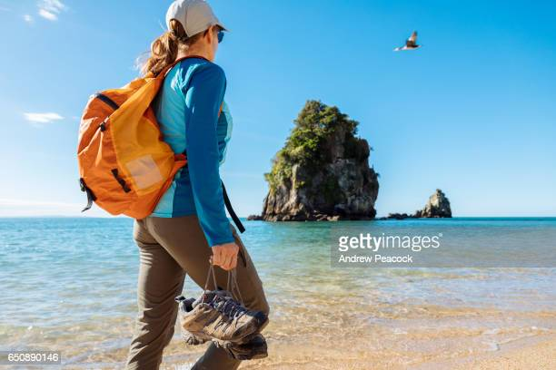 A woman walks on the beach at Abel Tasman National Park