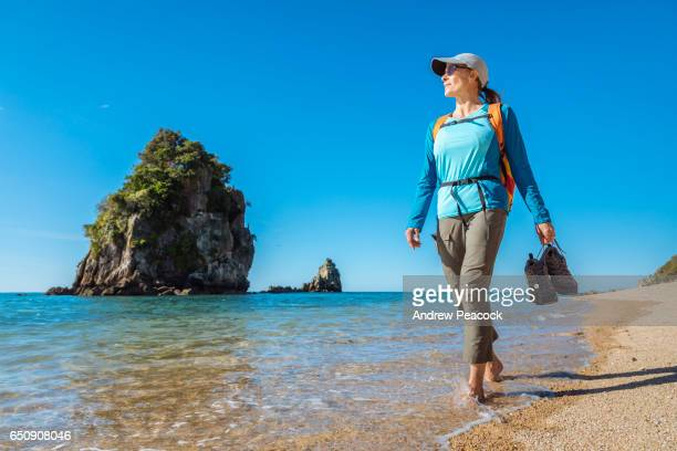 A woman walks on the beach at Abel Tasman National Park