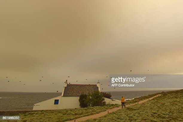 TOPSHOT A woman walks on the beach on October 16 in Quiberon western France as the sky turned a yellowochre colour due to sand from the Sahara desert...