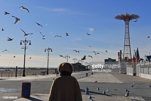 A woman walks on the Coney Island Boardwalk on a cold winter day in New York on January 22 2019 The hight temperature in New York was about 30F