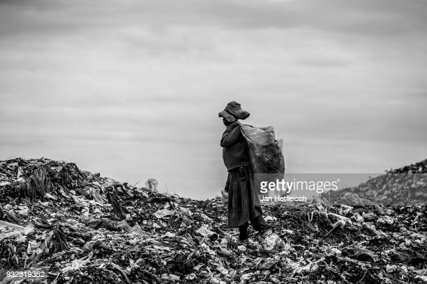 A woman walks on the Dandora rubbish Dump on March 14 2018 in Nairobi Kenya The Dandora landfield is located 8 Kilometer east of the city center of...