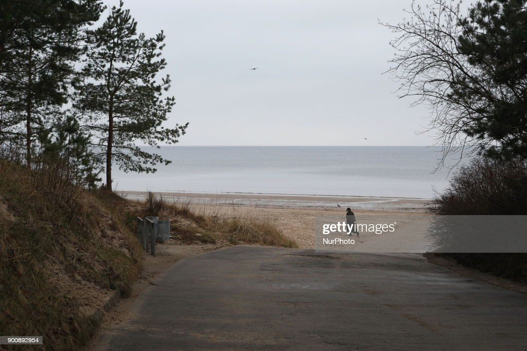 A woman walks on the embankment of the Gulf of Riga in Jurmala, 25 km from Riga. Latvia, Wednesday, January 3, 2018 The resort is famous for wooden Art Nouveau villas, Soviet-era sanatoriums and a long sandy beach.
