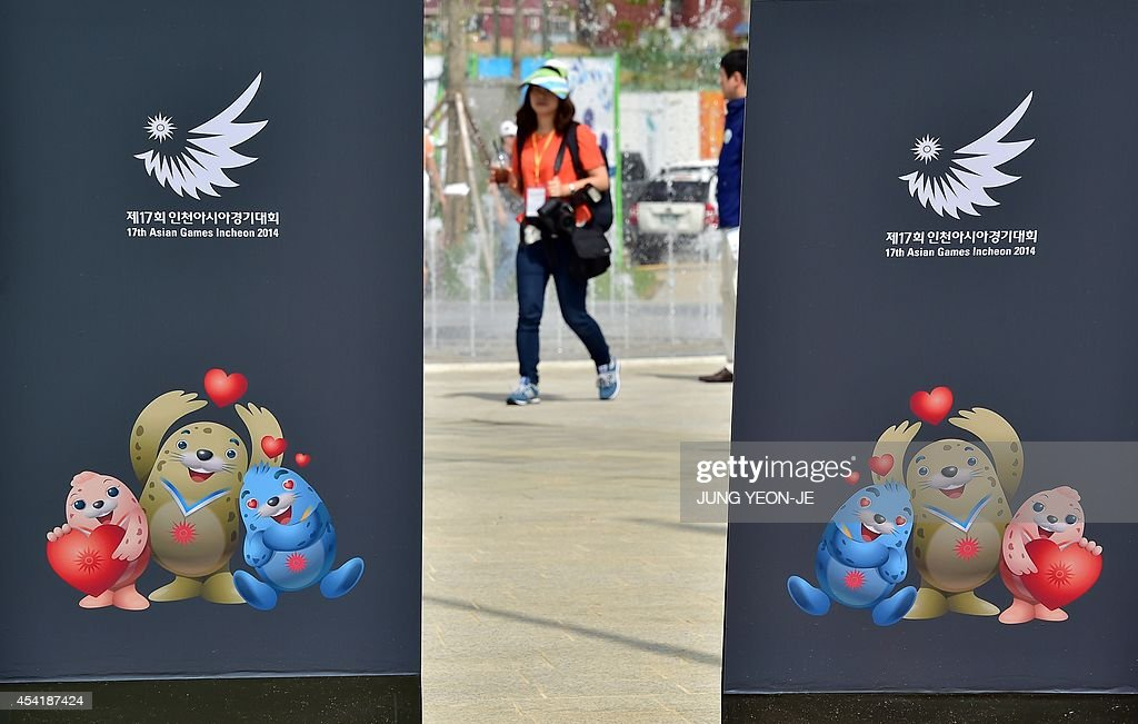 A woman walks on the flag plaza of the Athletes' Village for the upcoming 2014 Asian Games during a media tour in Incheon on August 26, 2014. The 2014 Asian Games will take place between September 19 and October 4, with Asia's top athletes competing across 36 sports.