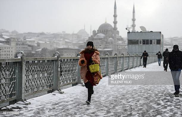 A woman walks on the Galata bridge in Istanbul on January 7 2015 Heavy snowfall descended on large parts of Turkey snarling road and air traffic and...