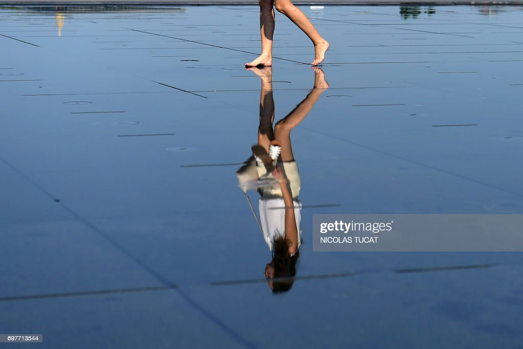 A woman walks on the pavement of the water mirror fountain, whose system alternates a mirror effect with a mist effect, on June 19, 2017 in Bordeaux's city center, southwestern France. French national meteorological service, Meteo France has placed 16 departments on orange alert for heatwaves, with temperatures between 33°C et 38°C expected in the Paris region and southwestern France. /