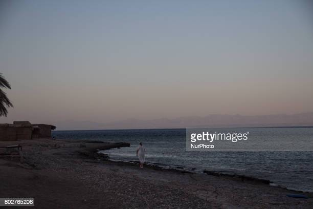 A woman walks on the shore of Aqaba's gulf in a Beduin camp near Nuweibaa on June 5 2017