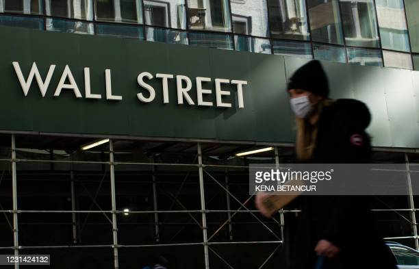 Woman walks on Wall Street in New York on February 8, 2021. - Pin-up photos and smutty jokes have long been commonplace on trading floors, but the...