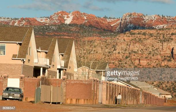 A woman walks ouside a large wall surrounding the compound of Warren Jeff's the prophet leader of the Fundamentalist Church of Jesus Christ of Latter...