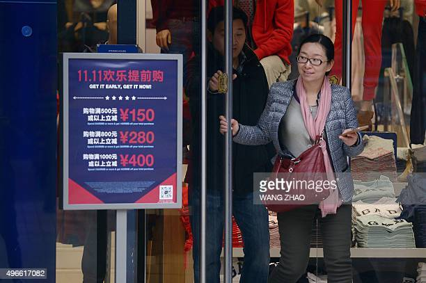 A woman walks out a shop past a 'Singles Day' sales promotional board in Beijing on November 11 2015 Shoppers spent around 9 billion USD in the first...