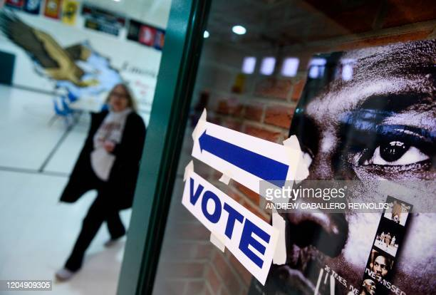 A woman walks out after voting in the Virginia Democratic primary at Emerick Elementary school in Purcellville Virginia on March 3 2020 Fourteen...