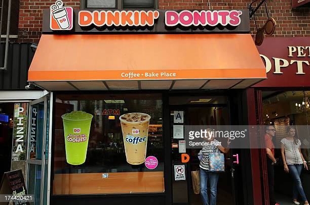 A woman walks out of a Dunkin' Donuts on July 25 2013 in New York City In a surprise to Wall Street Dunkin' Donuts reported a samestore sales rise of...