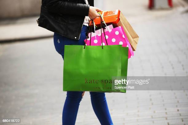 A woman walks out of a Kate Spade store in the SoHo neighborhood of Manhattan on May 8 2017 in New York City Coach the American maker of highend...