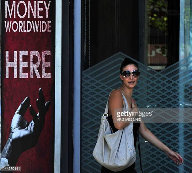 A woman walks out of a money exchange store in central Athens on August 08 2011 The Athens Stock Exchange opened with a loss and went on falling to...