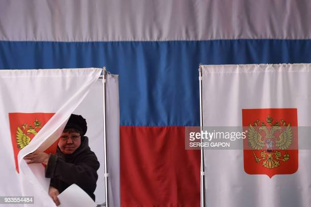 Woman walks out of a voting booth at a polling station during Russia's presidential election in the village of Novye Bateki, some 15 km north of...